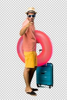 Mann mit hut und sonnenbrille in seinen sommerferien verärgert in wütender geste. frustriert von einer schlechten situation und nach vorne zeigend