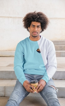 Mann mit kaffee, der hoodie trägt