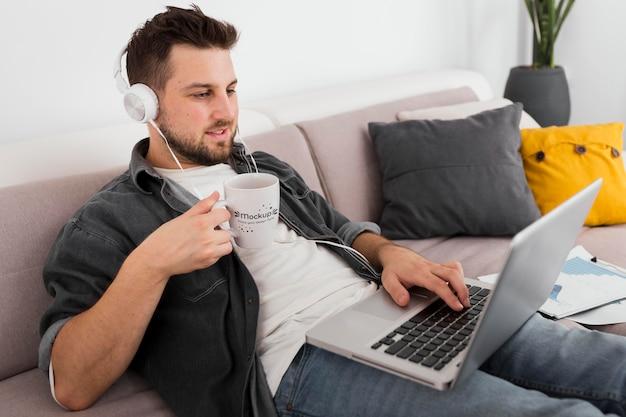 Mann mit laptop, der vom becher-modell trinkt