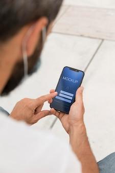 Mann mit maske auf der straße, die online am telefon liest