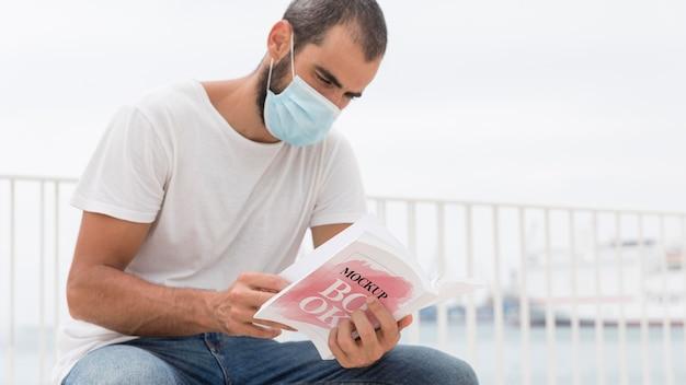 Mann mit maske auf straßenlesebuch