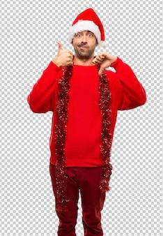 Mann mit roter kleidung die weihnachtsfeiertage feiern, die gut-schlechtes zeichen machen.