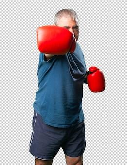 Mann mittleren alters, der sich mit boxhandschuhen locht
