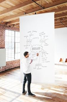 Mann schreibt auf ein weißes plakatmodell m