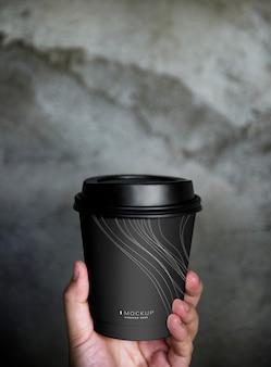 Menschliche hand, die eine modellkaffeetasse hält