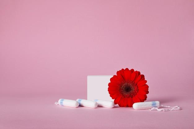 Menstruationstampons und rote blume lokalisiert auf rosa tabelle, draufsicht. speicherplatz kopieren