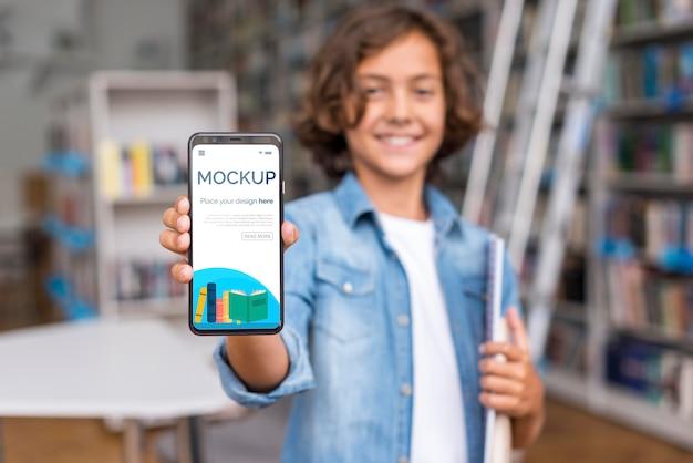 Mid shot boy in der bibliothek zeigt mock-up-telefon