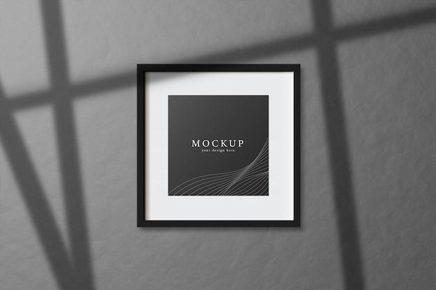 Minimales leeres quadratisches weißes rahmenbildmodell, das auf dunklem wandhintergrund mit fensterlicht und schatten hängt. vektorillustration isolieren.