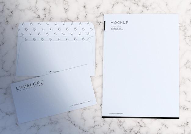 Minimalistischer weißer umschlag und briefkopf-satzmodell mit weißem marmorhintergrund