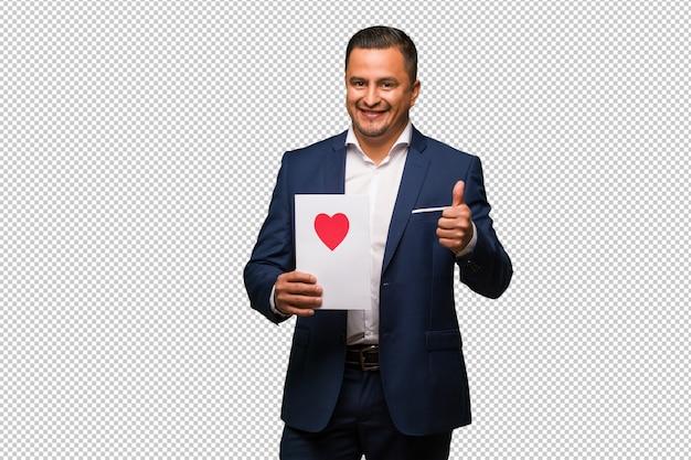 Mitte gealterter lateinischer mann, der den valentinsgrußtag oben lächelt und anhebt