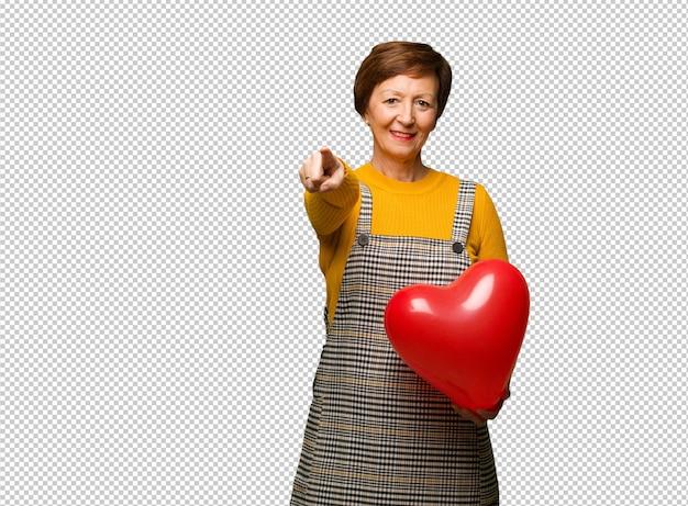 Mittlere gealterte frau, die den valentinsgrußtag nett und lächelnd feiert