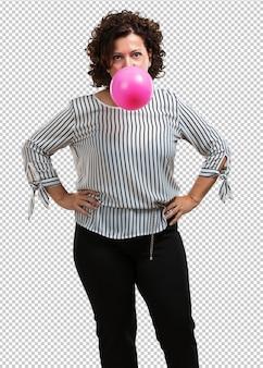 Mittlere greisin glücklich und fröhlich, einen kaugummiballon einschließend, sehr spielerisch und süß, spaßkonzept