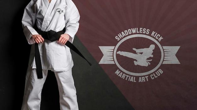 Mittlere schussfrau, die ihr karategürtelmodell hält