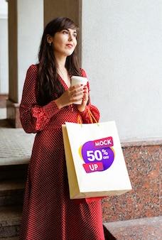 Mittlere schussfrau, die tasche und kaffeetasse hält