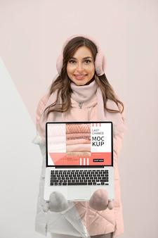 Mittlere schussfrau mit warmer kleidung und laptop
