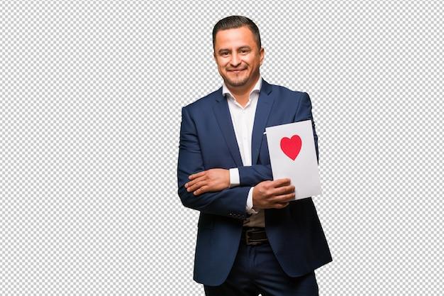 Mittlerer gealterter lateinischer mann, der valentinsgrußtagesüberfahrtarme feiert, lächelnd und entspannt