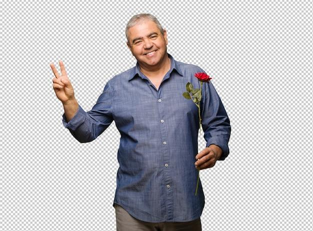 Mittlerer gealterter mann, der den valentinsgrußtag tut, der eine geste des sieges tut