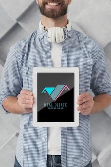 Mittlerer schuss des geschäftsmannes eine tablette mit immobilien halten