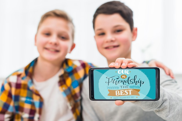 Mittlerer schuss glückliche jungen mit smartphone