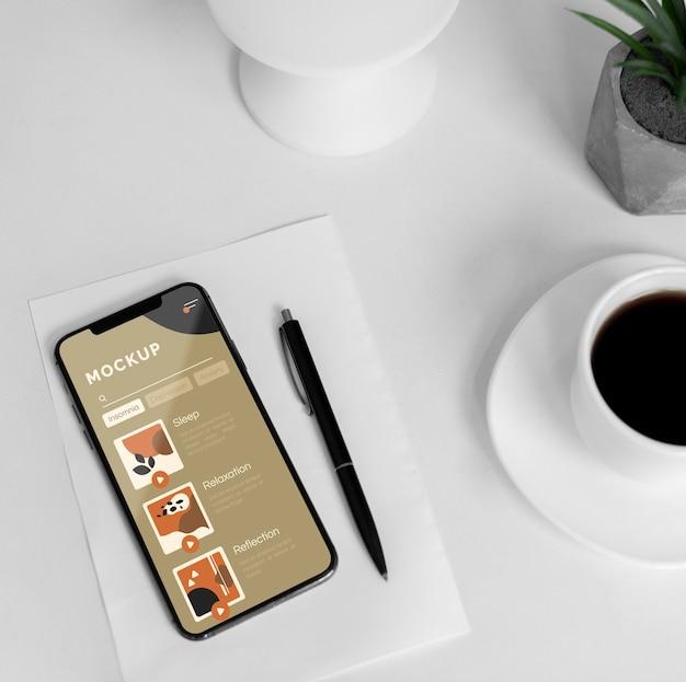 Mobil auf dem schreibtisch mit einer tasse kaffee