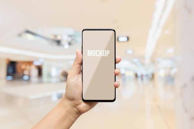 Mobiles smartphone des leeren weißen bildschirms des modells mit unscharfem hintergrund des modernen luxuskaufhauses