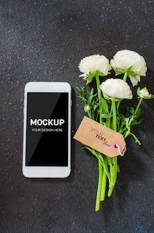 Mock-up des smartphone-bildschirms und der weißen blumen mit etikett auf dunkler betonwand. Premium PSD