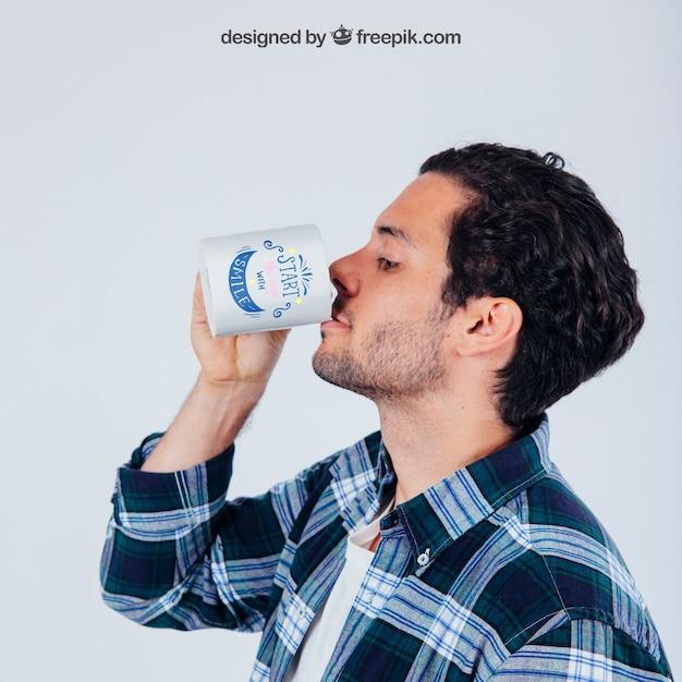 Mock up design der jungen mand trinken mit kaffeetasse