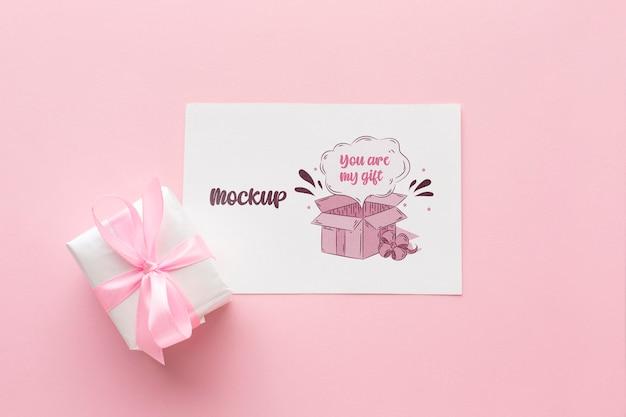 Mock-up niedliche karte mit verpacktem geschenk
