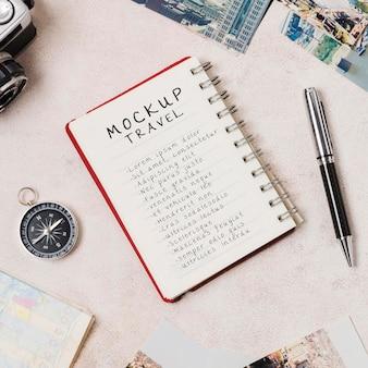 Mock-up-reise auf einem notizbuch mit kompass und stift