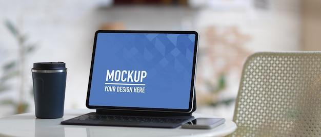 Mockup digital tablet mit tastatur und kaffeetasse auf couchtisch