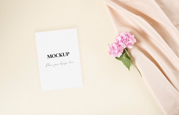 Mockup-hochzeitseinladungskarte mit rosafarbenen hortensienblüten aus nacktem stoff auf dem beigefarbenen hintergrund