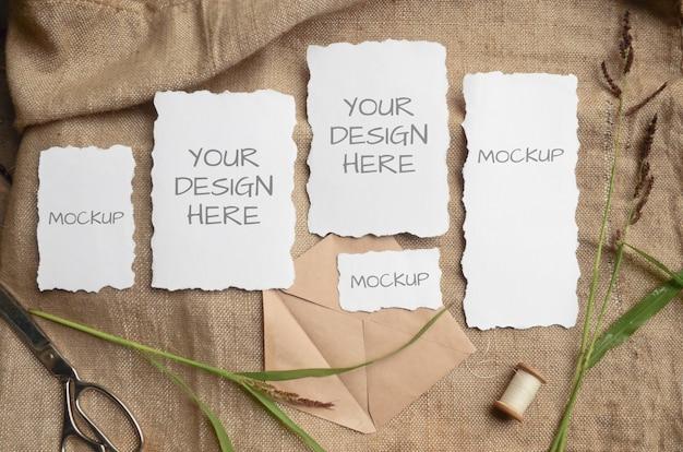 Mockup-karte grußkarte oder hochzeitseinladung mit gezackten kanten mit kräutern, vintage-spule auf einem beigen raum aus sackleinen stoff