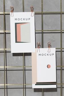 Mockup-karten hängen an gitter-memo-tafel mit clips
