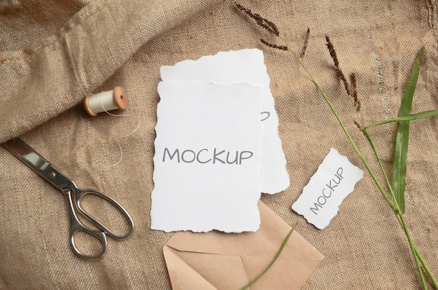 Mockup-kartengrußkarte oder hochzeitseinladung mit gezackten kanten mit kräutern, weinlesespule auf beige