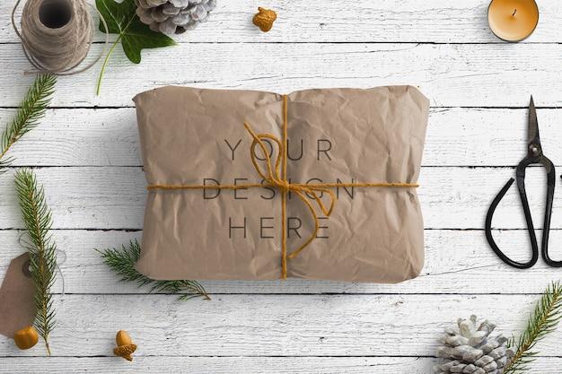 Mockup winter naturszene mit braunem paket und geschenkartikeln