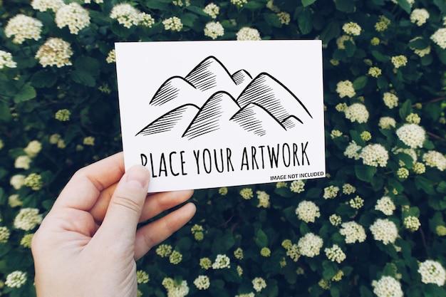 Modell der hand, die vertikale postkarte auf unscharfem weißem frühlingsblumenhintergrund hält