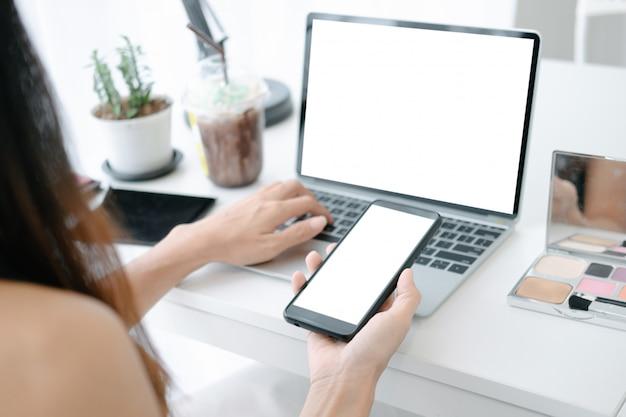 Modell der schönheit online kaufend mit laptop und smartphone auf on-line-website