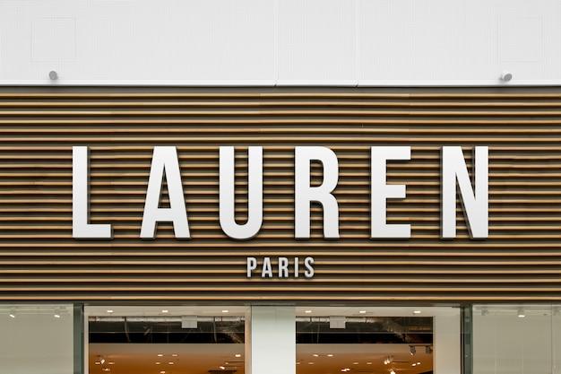 Modell des exklusiven eleganten weißen logozeichens der mode 3d auf hölzerner shopfassade oder schaufenstereingang