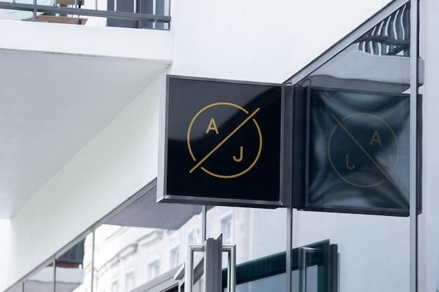 Modell des modernen hängenden logozeichens des schwarzen quadrats auf unternehmensgebäudefassade oder -schaufenster