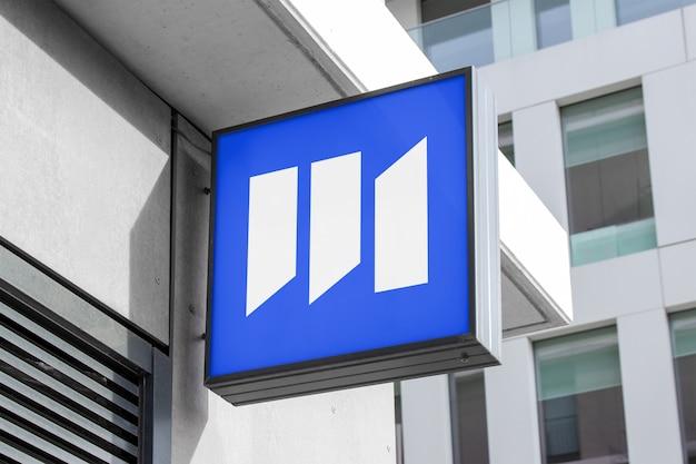 Modell des modernen quadratischen hängenden logozeichens auf unternehmensgebäude im schwarzen rahmen