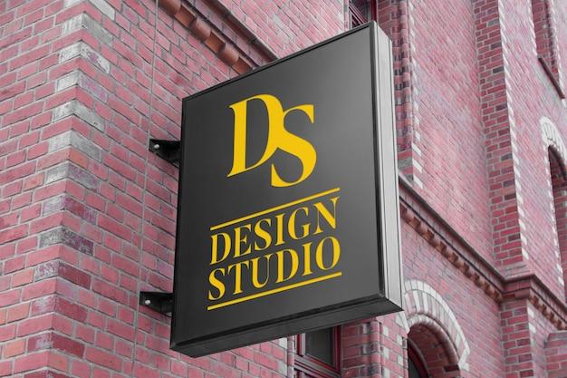 Modell des modernen vertikalen schwarzen hängenden logozeichens auf klassischer gebäudefassade der wand des roten backsteins