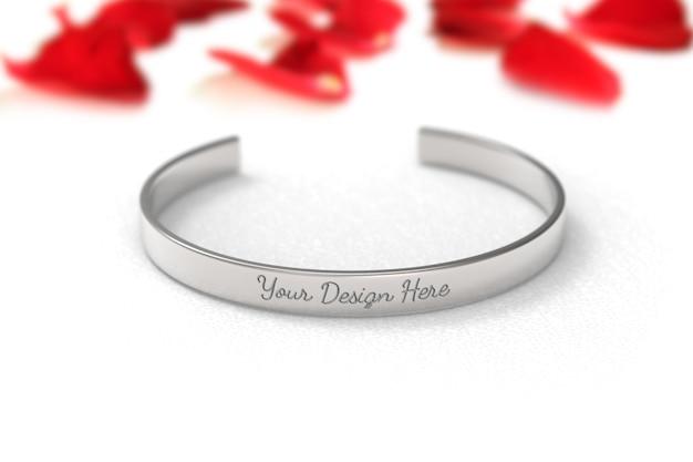 Modell des silberfarbenen metallarmbandes auf weißem hintergrund mit rosenblättern.