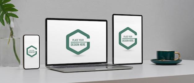 Modell digitaler geräte auf dem arbeitstisch mit smartphone, laptop und digitalem tablet