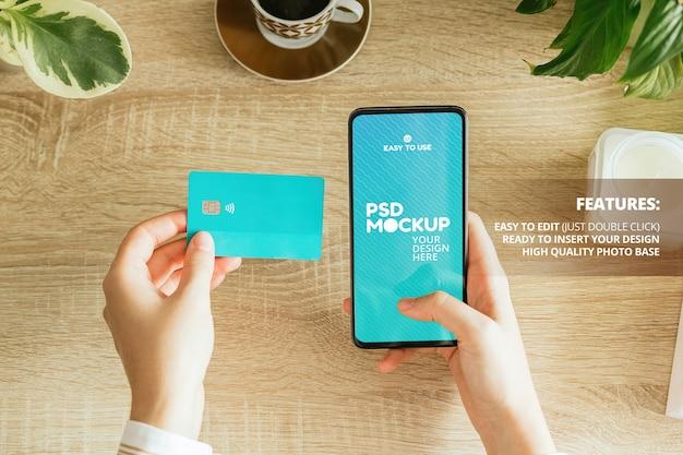 Modell einer frau, die ein telefon und eine kreditkarte auf dem tisch hält