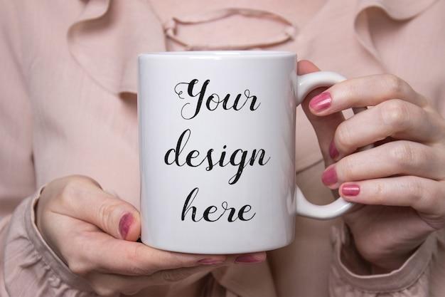 Modell einer weißen keramikkaffeetasse in den händen