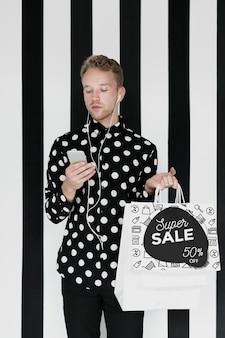 Modell gutaussehender mann, der einkaufstaschen hält