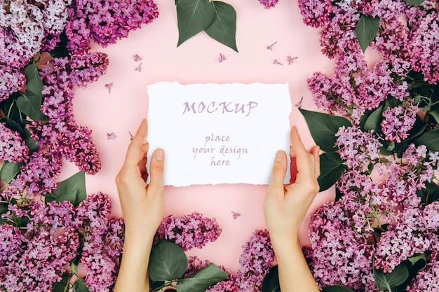 Modell mit einer postkarte in den frauenhänden auf einem rosa hintergrund mit blühenden lila zweigen
