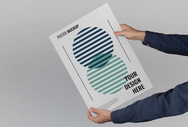 Modell von händen, die ein großformatiges poster auf einem flachen hintergrund halten