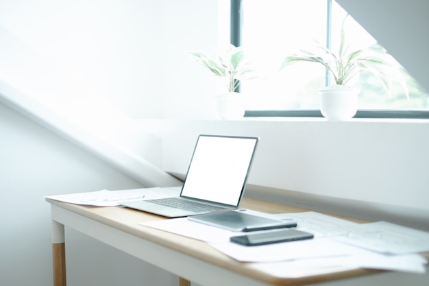 Modellbild des laptops auf hölzerner tabelle mit ausrüstung des grafikdesigners der beweglichen anwendung