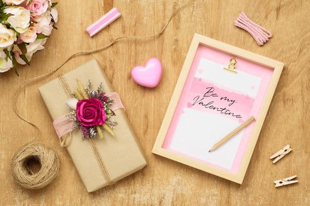 Modellfoto framewith handwerksgeschenkbox und rosafarbene blumen auf holz
